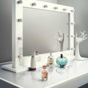 Deze make-up spiegel heeft een rondom geplaatst hoogglans houten kader waarin de lampen verzonken liggen, erg fraai!