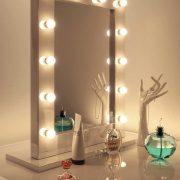 Deze spiegel is rondom voorzien van een fraai, hooglans wit kader waar de lampen deels in verzonken liggen